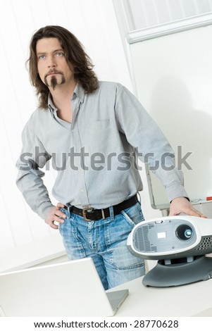 Casual businessman doing presentation using video projector and laptop computer. - stock photo