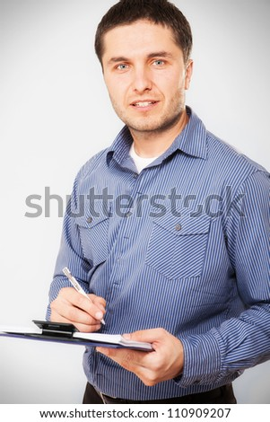 Casual businessman holding a clipboard - stock photo