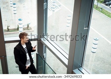 Casual businessman holding mobile and typing message. He is standing in front of a big window and looking outside.  - stock photo