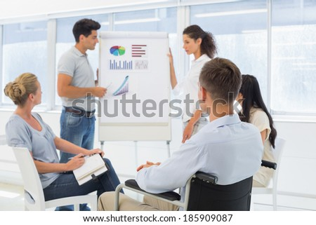 Casual businessman in wheelchair listening to presentation in the office - stock photo
