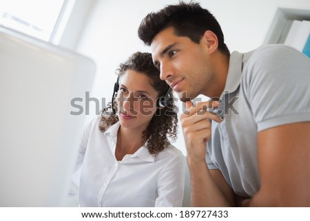 Casual businessman looking at colleagues computer in the office - stock photo