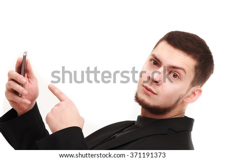 Casual businessman pointing with a finger at the phone with a raised eyebrow - stock photo