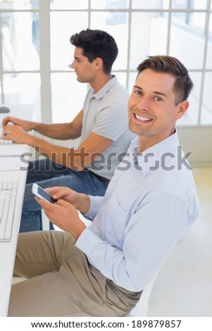 Casual businessman sending a text at his desk in the office - stock photo