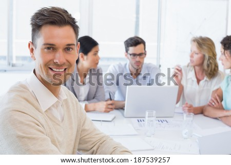 Casual businessman smiling at camera during meeting in the office - stock photo