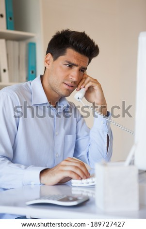 Casual businessman talking on the telephone in his office - stock photo