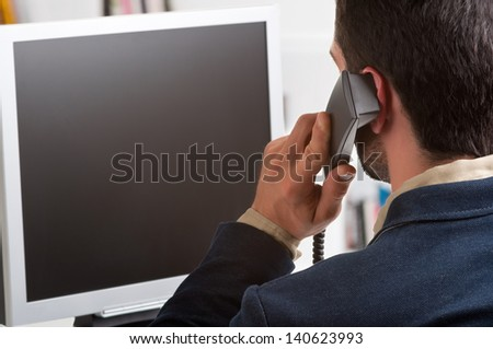Casual businessman talking over the phone and looking at an empty computer screen - stock photo