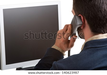 Casual businessman talking over the phone and looking at an empty computer screen, isolated in white - stock photo