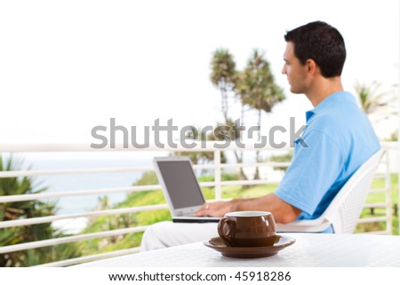casual businessman using laptop on balcony with sea view behind, shallow focus on the coffee cup - stock photo