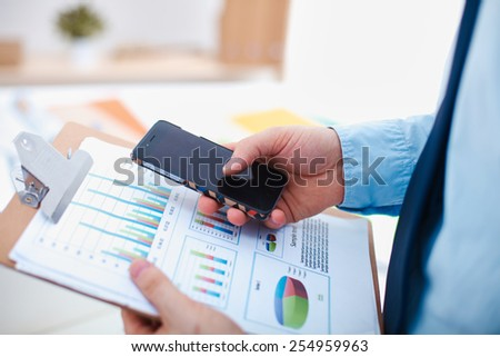 Casual businessman using mobile phone at modern stylish office - stock photo