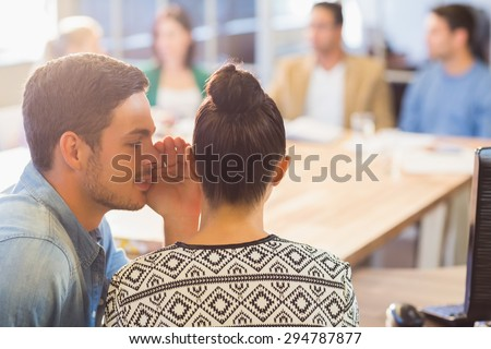 Casual businessman whispering secret to his colleague in the office - stock photo