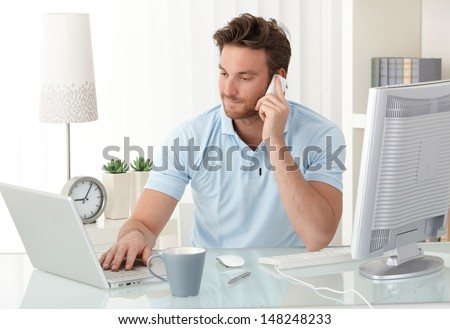 Casual businessman working at office desk, using mobile phone and laptop computer, typing, making phone call, smiling. - stock photo