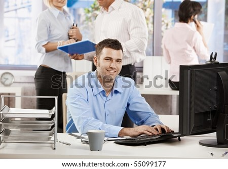 Casual businessman working with computer in office, looking at camera, smiling.? - stock photo