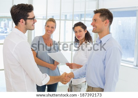 Casual businessmen shaking hands and smiling in the office - stock photo
