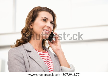 Casual businesswoman having a phone call in the office - stock photo