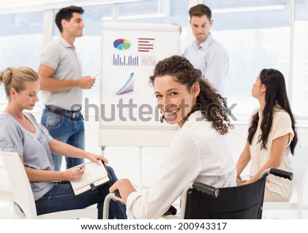 Casual businesswoman in wheelchair smiling at camera during meeting in the office - stock photo