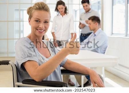 Casual businesswoman in wheelchair smiling at camera with team behind her in the office - stock photo