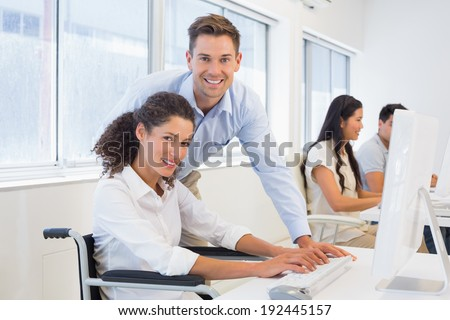 Casual businesswoman in wheelchair working at her desk with colleague in the office - stock photo