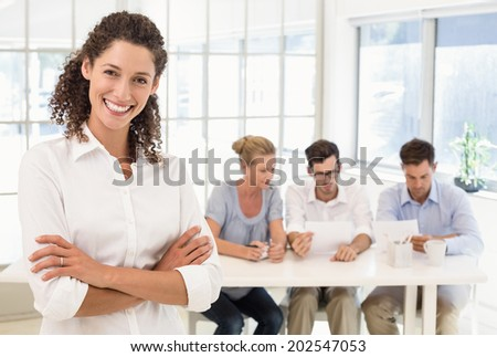 Casual businesswoman smiling at camera with team behind her in the office - stock photo