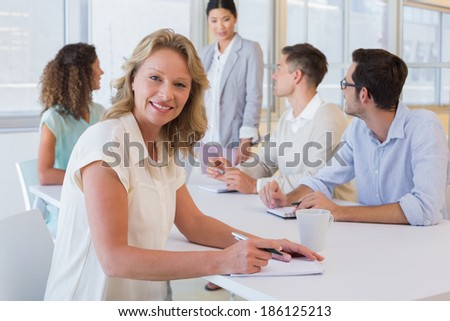 Casual businesswoman taking notes during meeting in the office - stock photo