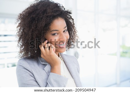 Casual businesswoman talking on phone in her office - stock photo