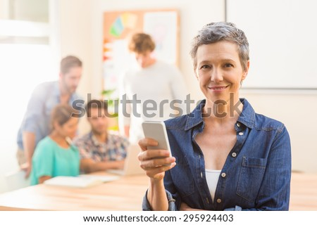 Casual businesswoman using her smartphone in the office - stock photo