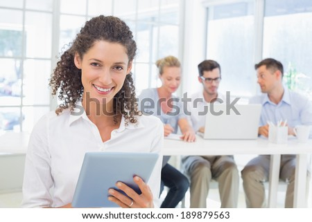 Casual businesswoman using tablet with team behind her in the office - stock photo