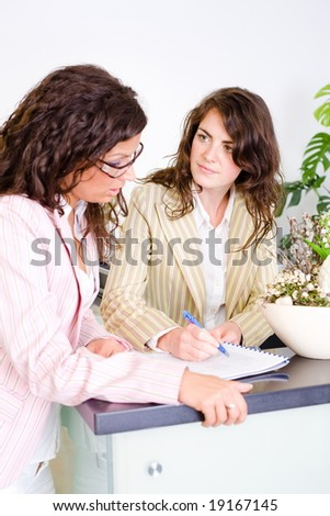 Casual businesswomen working together in team at office reception, looking at documents, talking. - stock photo