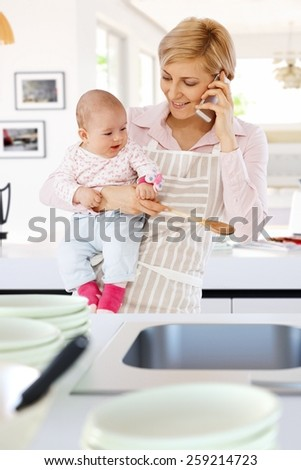 Casual caucasian housewife in kitchen with baby, phone, spoon in hand. Standing, smiling, talking on phone. - stock photo