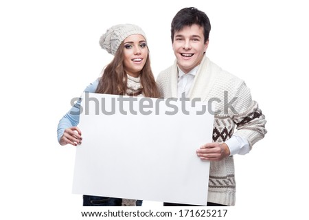 casual caucasian young couple in winter clothing holding big sign. isolated on white - stock photo