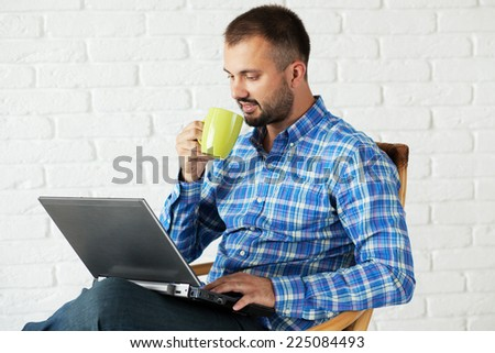 Casual cheerful man working with laptop and drinking a tea - stock photo