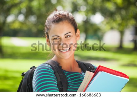 Casual cheerful student holding books on campus at college - stock photo