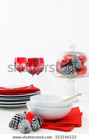 Casual christmas table setting crockery display in red and white theme, pine cones, xmas baubles decorations - stock photo