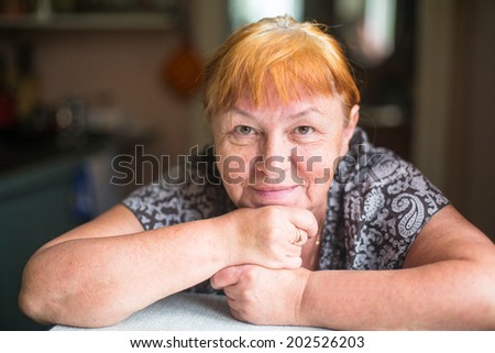 Casual close-up portrait of happy mature woman with red hair and minimal makeup. - stock photo