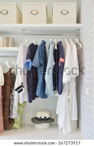 Casual cloths hanging in open wardrobe at modern home - stock photo
