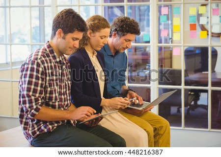 Casual colleagues using technology in the office - stock photo