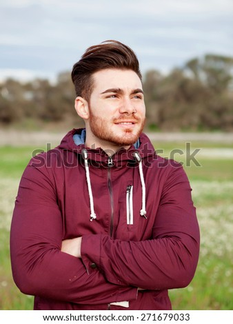 Casual cool young man with beard in the field - stock photo