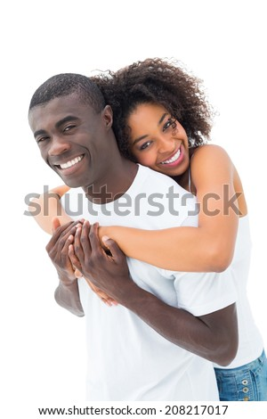 Casual couple hugging and smiling at camera on white background - stock photo