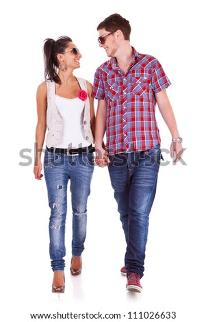 Casual couple is walking towards the camera looking at each other, on white - stock photo