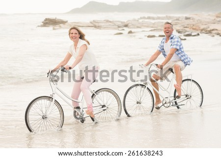 Casual couple on a bike ride at the beach - stock photo