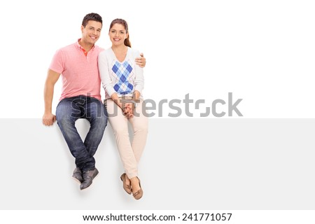 Casual couple posing seated on a blank panel isolated on white background - stock photo