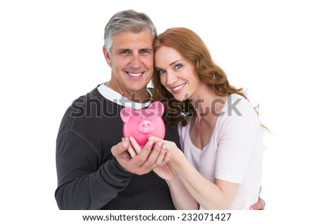 Casual couple showing their piggy bank on white background - stock photo