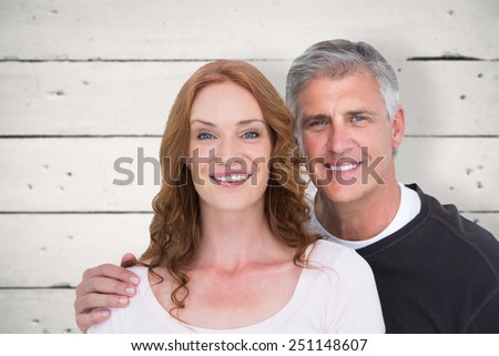 Casual couple smiling at camera against white wood - stock photo