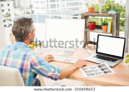 Casual designer working on computer in the office - stock photo