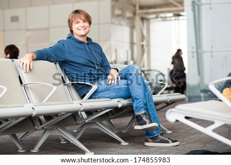 casual dressed handsome young man waiting for flight at airport - stock photo