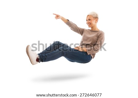 Casual dressed woman is floating while indicating a direction over white isolated background - stock photo