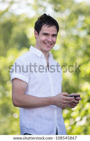 Casual Dressed Young Man Texting on Cell Phone Outdoor Smiling - stock photo
