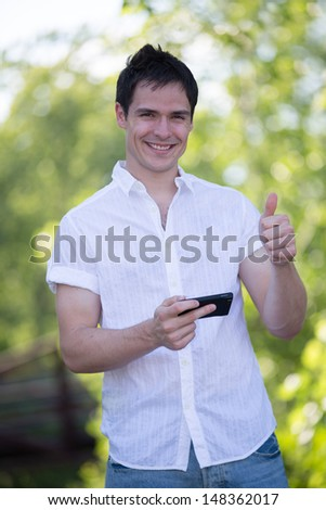 Casual Dressed Young Student Texting on Cell Phone Outdoor Smiling - stock photo