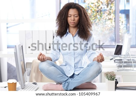 Casual ethnic office worker sitting on top of desk, relaxing eyes closed. - stock photo