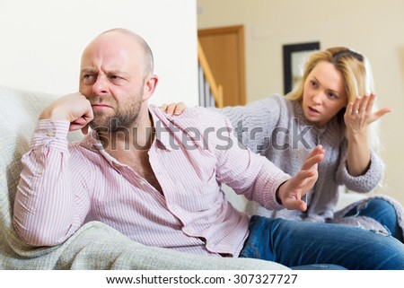 Casual family having quarrel in livingroom at home - stock photo