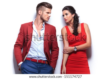 casual fashion man and woman looking at each other while leaning against white wall - stock photo